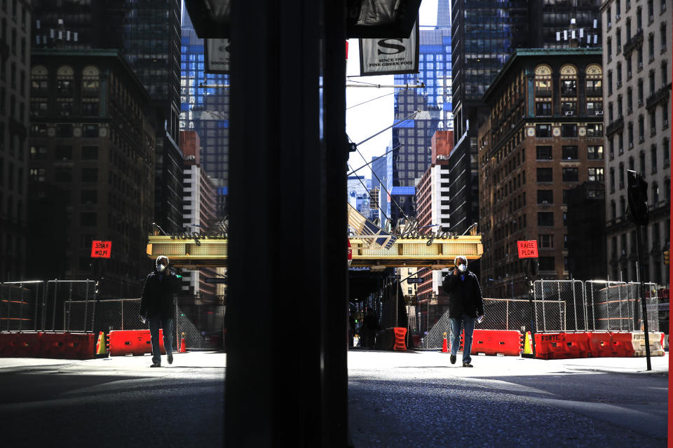 A person wearing a protective face mask walks in New York, Monday, April 6, 2020, during the current coronavirus outbreak. (AP Photo/Matt Rourke)