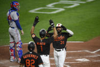 Baltimore Orioles' Cedric Mullins (31) celebrates his three-run home run with Richie Martin (1) and Kelvin Gutierrez (82) during the second inning of a baseball game against the Texas Rangers, Friday, Sept. 24, 2021, in Baltimore. Rangers catcher Jonah Heim, top left, looks on. (AP Photo/Nick Wass)