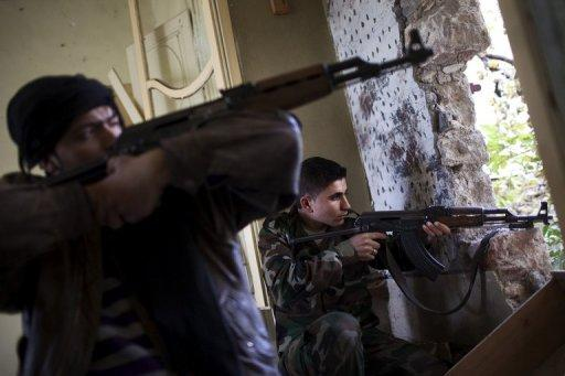 Rebel fighters aim their weapons at regime forces on the front line in the old city of Aleppo on December 21, 2012