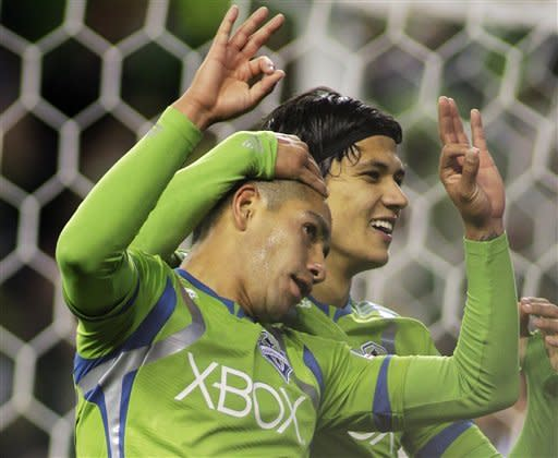 Seattle Sounders' David Estrada, left, celebrates with teammate Fredy Montero after his third goal against Toronto FC in an MLS soccer game, Saturday, March 17, 2012, in Seattle. (AP Photo/Ted S. Warren)
