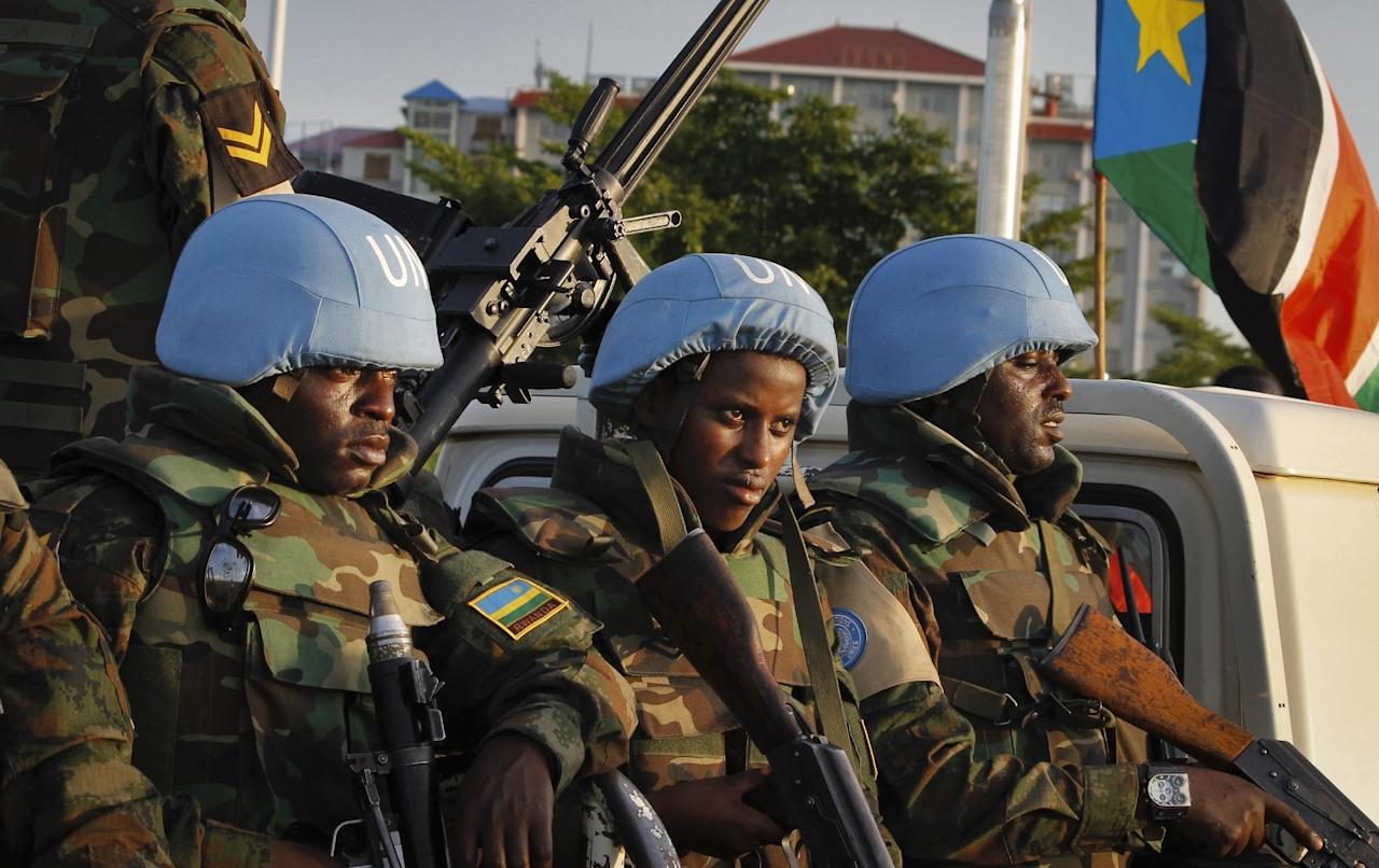 "FILE - In this Friday, Sept. 2, 2016 file photo, United Nations peacekeepers from Rwanda wait to escort members of the U.N. Security Council as they arrive at the airport in the capital Juba, South Sudan. Minister of Cabinet Affairs Martin Lomuro said Saturday, Nov. 26, 2016 that the government has accepted to have with ""no conditions"" an increased peacekeeping force as mandated by the U.N. Security Council in August. (AP Photo/Justin Lynch, File)"