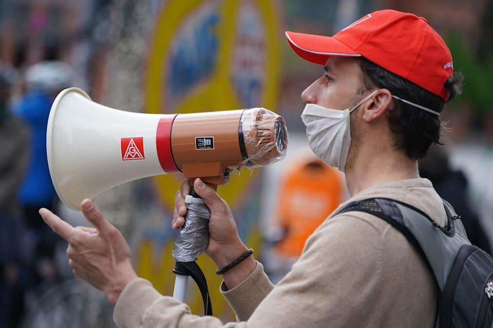 BERLIN, GERMANY - MAY 01: A member of the IG Metall labor union wears a protective face mask as he speaks into a megaphone covered with plastic wrap at a demonstration on May Day at Potsdamer Platz during the novel coronavirus crisis on May 1, 2020 in Berlin, Germany. May Day protests are taking place across Germany today, though as gatherings are limited by authorities to a maximum of 20 people per gathering due to coronavirus lockdown measures, many small protests are taking place instead of traditional, large-scale marches. (Photo by Sean Gallup/Getty Images)