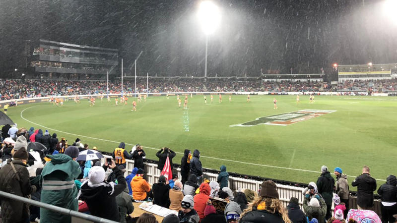 Fans at Friday night's AFL clash between the GWS Giants and Hawthorn at Canberra's Manuka Stadium had to contend with snow falling in the first quarter. Picture: Twitter/@WG_Cooper