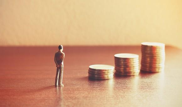 A miniature figurine of a man is standing on a table in front of three stacks of coins.