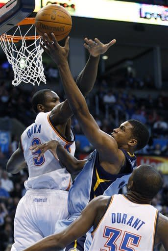 Memphis Grizzlies forward Rudy Gay, center, shoots between Oklahoma City Thunder forward Serge Ibaka (9), of the Republic of Congo, and forward Kevin Durant (35) in the first quarter of an NBA basketball game in Oklahoma City, Friday, Feb. 3, 2012. (AP Photo/Sue Ogrocki)