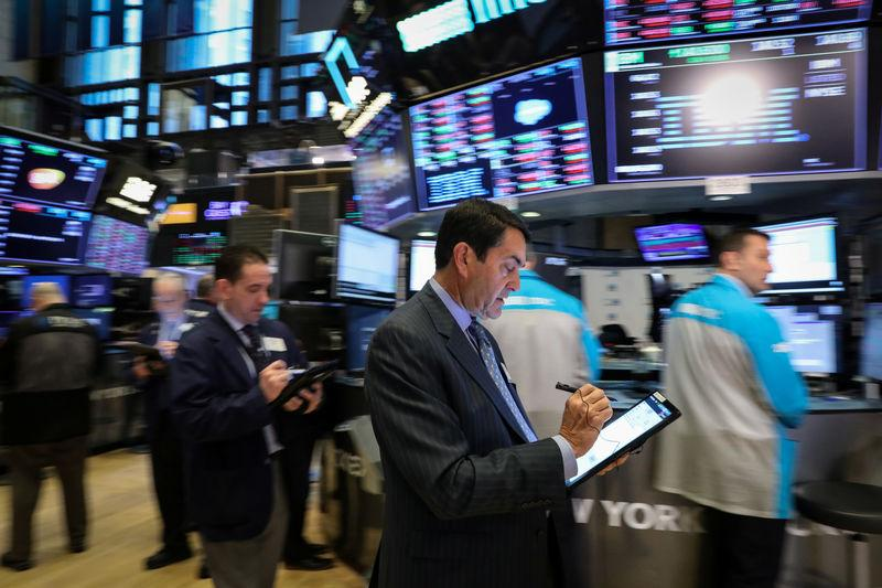 FILE PHOTO: Traders work on the floor at the New York Stock Exchange (NYSE) in New York, U.S., March 20, 2019. REUTERS/Brendan McDermid