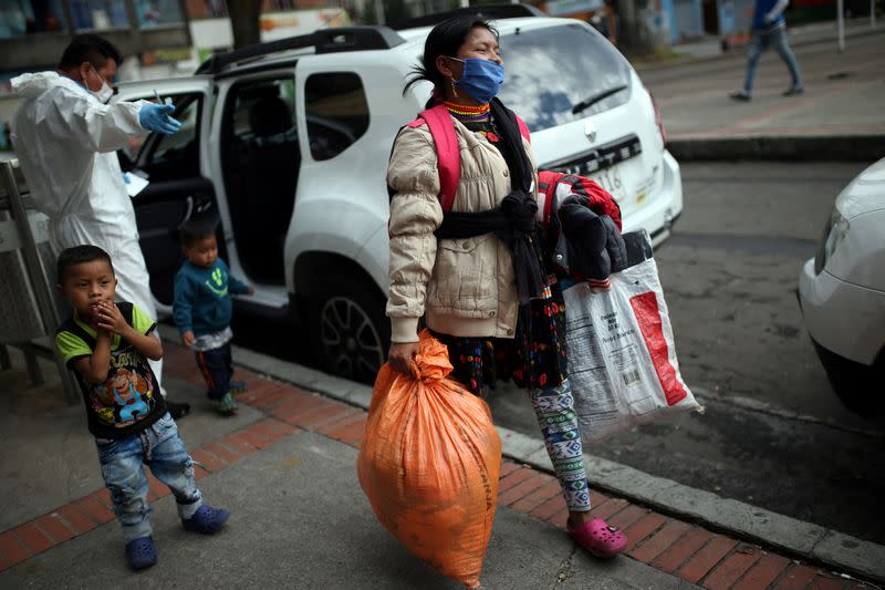 An indigenous woman wearing a protective face mask as a preventive measure against the spread of the coronavirus disease (COVID-19) carries her belongings after being evicted from a building in Bogota