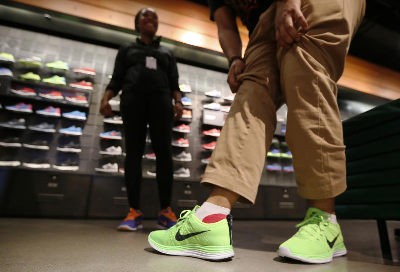A man tries on shoes in the Nike store in Santa Monica, California, September 25, 2013. NIKE, Inc. plans to release its first quarter fiscal 2014 financial results on Thursday, September 26, 2013. REUTERS/Lucy Nicholson (UNITED STATES - Tags: BUSINESS SPORT)