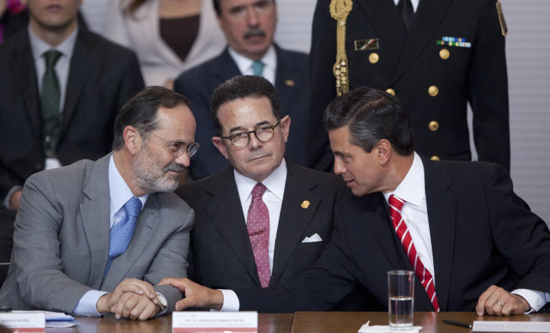 Mexico's President Enrique Pena Nieto, right, speaks to Mexican Senate Deputy Chairman Francisco Arroyo Vieira, center, and President of the National Action Party (PAN) Gustavo Madero, left, during an event to sign an agreement with the three major political parties that would create two new national television channels and form a powerful independent regulatory commission along the lines of the U.S. Federal Communications Commission, at the Technological Museum in Mexico City, Monday, March 11, 2013. Pena Nieto on Monday proposed a sweeping overhaul of the weak and chaotic regulations that have allowed the world's richest man and the largest Spanish-language media empire to exert near-total control of Mexico's lucrative telephone and television markets. (AP Photo/Alexandre Meneghini)