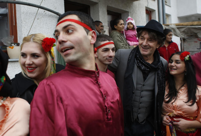 Bosnian Roma people showcase a national dance during a visit by Bosnia's most popular former rock star, now composer of ethnic music inspired by Roma culture, Goran Bregovic, second from right, in Sarajevo, on Tuesday, Dec. 10, 2013. Bosnia's most popular musician is searching for talented Roma children to help them get an education in music. On Tuesday, 63-year-old former rock star Goran Bregovic visited Sarajevo's biggest Roma settlement of Gorica. That's the same name he has given his new foundation, which will provide scholarships to Roma kids who wish to study music but can't afford to. (AP Photo/Amel Emric)