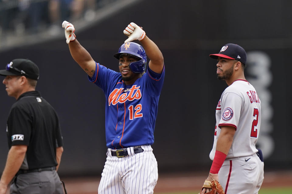 Washington Nationals shortstop Luis Garcia (2) looks on as New York Mets' Francisco Lindor (12) gestures after his double scored Patrick Mazeika and Jonathan Villa during the eighth inning of a baseball game Sunday, Aug. 29, 2021, in New York. (AP Photo/Corey Sipkin)