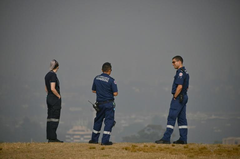 Paramedics take a break as they look out over a smokey haze which blankets Sydney. (AFP Photo/PETER PARKS)