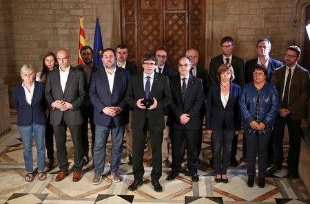 Catalan Regional President Carles Puigdemont (C) is flanked by members of his government as he makes an statement at Generalitat Palace in Barcelona, Spain, October 1, 2017. Catalan Goverment/Jordi Bedmar Pascual/Handout via REUTERS