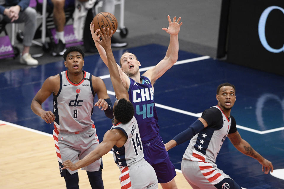 Charlotte Hornets center Cody Zeller (40) battles for the ball against Washington Wizards guard Ish Smith (14) during the first half of an NBA basketball game, Sunday, May 16, 2021, in Washington. Wizards forward Rui Hachimura (8) and center Daniel Gafford, right, look on. (AP Photo/Nick Wass)