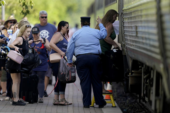 FILE - In this June 11, 2021, file photo, passengers board a Missouri River Runner Amtrak train in Lee's Summit, Mo. As the U.S. emerges from the COVID-19 crisis, Missouri is becoming a cautionary tale for the rest of the country: It is seeing an alarming rise in cases because of a combination of the fast-spreading delta variant and stubborn resistance among many people to getting vaccinated. (AP Photo/Charlie Riedel, File)