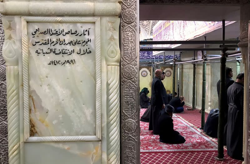Iraqis pray at the shrine of the Imam Hussein, next to a plaque that frames the bullet holes where Saddam Hussein's forces killed Shi'ite opposition during an uprising in 1991, in the holy city of Kerbala