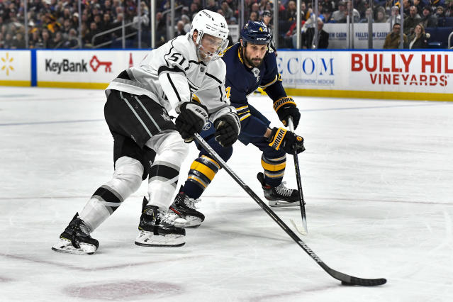 Los Angeles Kings left wing Austin Wagner, left, is defended by Buffalo Sabres defenseman Zach Bogosian during the first period of an NHL hockey game in Buffalo, N.Y., Saturday, Dec. 21, 2019. (AP Photo/Adrian Kraus)