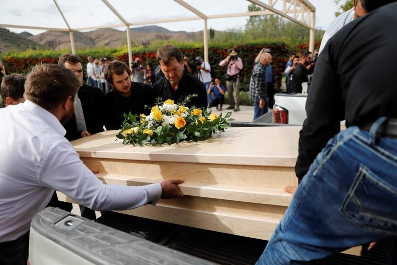 Relatives carry one of the coffins of Dawna Ray Langford and her sons Trevor and Rogan, who were killed by unknown assailants, to be buried at the cemetery in La Mora