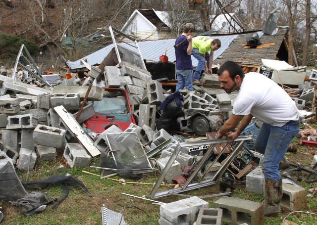 Justin Chandler searches through debris of his brother-n-law's shop after a tornado ripped through early Wednesdy morning Jan. 30, 2013, destroying several homes and businesses in Coble, TN. (AP Photo/Butch Dill)