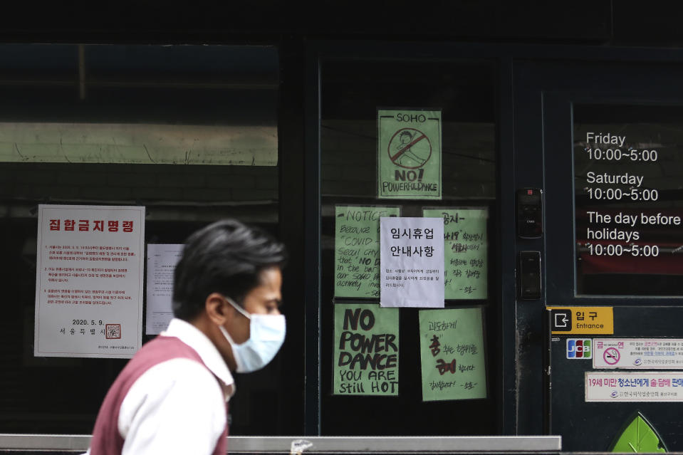 "A man waring a face mask passes by notices at the entrance of a temporary closed dance club in Seoul, South Korea, Sunday, May 10, 2020. South Korea on Friday advised nightclubs and similar entertainment venues to close for a month and may delay the reopening of schools after linking more than a dozen new coronavirus infections to clubgoers in the capital. The signs read "" Temporary closed,"" right and ""the Seoul city emergency administrative order to prohibit gathering,"" left. (AP Photo/Ahn Young-joon)"