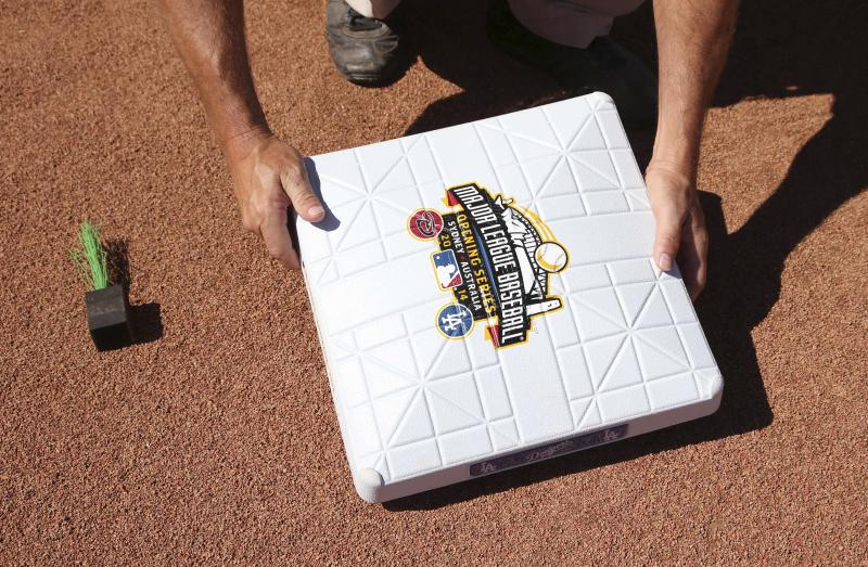 A base with a commemorative logo is placed on the diamond as preparations are made for the Major League Baseball opening game between the Los Angeles Dodgers and the Arizona Diamondbacks at the Sydney Cricket ground in Sydney, Saturday, March 22, 2014. (AP Photo/Rick Rycroft)