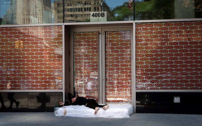 A homeless man lies on a mattress in Midtown Manhattan following the outbreak of the coronavirus disease (COVID-19) in New York - Reuters