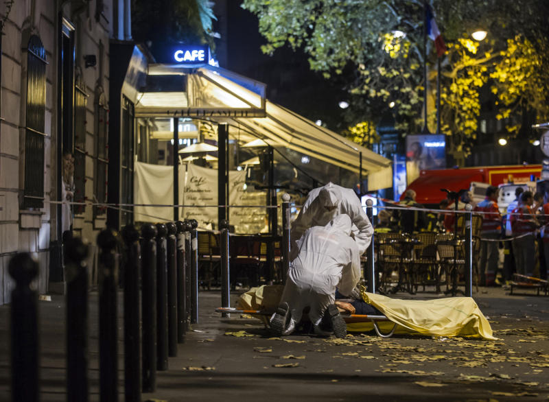 FILE - In this Nov.13, 2015 file photo, investigating police officers inspect the lifeless body of a victim of a shooting attack outside the Bataclan concert hall in Paris. France is commemorating the fourth anniversary of the Islamic State attacks in Paris. The attacks on Nov. 13, 2015, left 131 people dead at the country's national stadium, the Bataclan concert hall and bars and restaurants in the city center. (AP Photo/Kamil Zihnioglu, File)