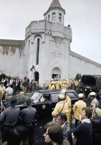 FILE - In this Sept. 13, 1971 file photo, prison guards and New York State troopers gather outside Attica State Prison as they prepare to enter the prison and retake it after inmates rioted and held the prison for five days, in Attica, Sept. 13, 1971. New York's Attorney General Eric Schneiderman has asked a state judge to unseal documents about the 1971 riot and retaking of Attica state prison in the nation's bloodiest prison rebellion. (AP Photo, File)