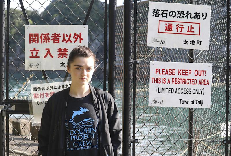 """In this photo released by DolphinProject, Maisie Williams stands in front of a fence with notice boards beside the beach known for dolphin hunting in Taiji, Wakayama prefecture, central Japan, Friday, Dec. 2, 2016. """"Game of Thrones"""" star Williams, 19, wants everyone to stop buying tickets to marine shows, the best way, she thinks, to stop the dolphin capture and killing in Japan. Williams spoke Friday from the small Japanese town of Taiji, made famous in """"The Cove"""" an Oscar-winning film that documented the dolphin hunt and starred Ric O'Barry, the dolphin trainer for the """"Flipper"""" TV series. (Lincoln O'Barry via AP)"""