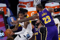 Memphis Grizzlies guard Ja Morant, left, tries to pass while under pressure from Los Angeles Lakers forward Anthony Davis, center, and forward LeBron James during the first half of an NBA basketball game Friday, Feb. 12, 2021, in Los Angeles. (AP Photo/Mark J. Terrill)