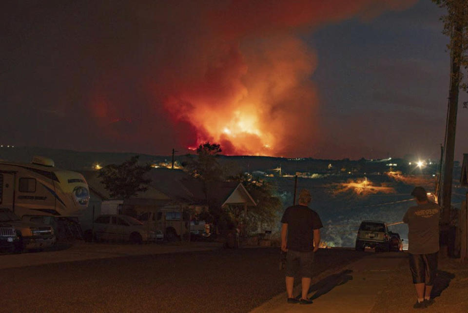 In this photo provided by Joseph Pacheco, a wildfire is seen burning in Globe, Ariz., on Monday, June 7, 2021. Firefighters in Arizona were fighting Tuesday to gain a foothold into a massive wildfire, one of two that has forced thousands of evacuations in rural towns and closed almost every major highway out of the area. (Joseph Pacheco via AP)