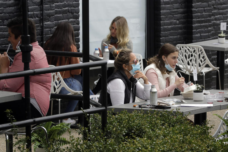 Patrons dine in an outdoor seating area at Plant City restaurant, Monday, May 18, 2020, in Providence, R.I. Rhode Island allowed restaurants to provide service with outdoor seated dinning Monday for the first time since the beginning of the government imposed lockdown due to the coronavirus pandemic. (AP Photo/Steven Senne)