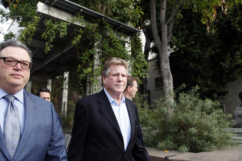 HOLD FOR STORY -- In this Monday, Dec. 2, 2013 file photo, actor Ryan O'Neal, right, leaves court after he testified in a Los Angeles courtroom about his relationship with Farrah Fawcett and his claimed ownership of an Andy Warhol portrait of the actress. The Warhol portrait of Fawcett belongs to O'Neal, a Los Angeles jury determined Thursday, Dec. 20, 2013. The verdict will allow O'Neal to keep the portrait in his beachside home, where he has said it remains a powerful reminder of his decades-long relationship with Fawcett. (AP Photo/Nick Ut, File)