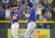 Chicago Cubs' Patrick Wisdom, front, claps as he reaches second base with a double that drove in three runs as Colorado Rockies second baseman Brendan Rodgers looks on in the fifth inning of a baseball game Wednesday, Aug. 4, 2021, in Denver. (AP Photo/David Zalubowski)