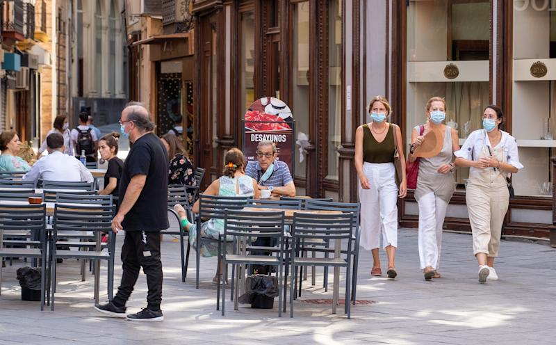 SEVILLA, SPAIN - JULY 15: Three women are seen walking with a hand fun and others are sitting at a coffe shop on the first day of mandatory use of masks in Seville on July 15, 2020 in Madrid, Spain. (Photo by Eduardo Briones/Europa Press via Getty Images)