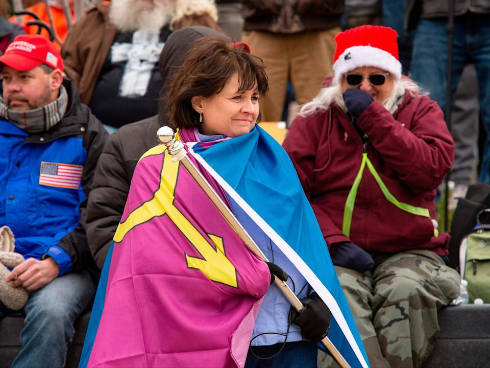"""<p>""""Super Fun Happy America's"""" Sue Ianni wraps herself in the group's """"Straight Pride"""" flag as she and other supporters of US President Donald Trump wait for him to address them during a rally in Washington, DC on 6 January 2021</p> ((AFP via Getty Images))"""