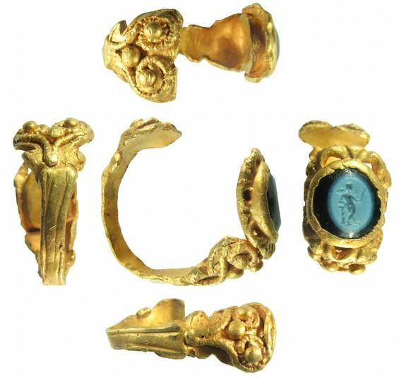 The ring's gold working is very intricate, including spiral designs and bead-shaped spheres.