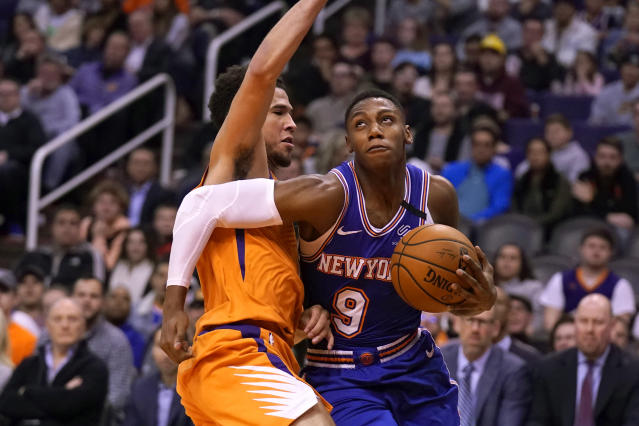 New York Knicks guard RJ Barrett (9) drives against Phoenix Suns guard Devin Booker in the first half during an NBA basketball game, Friday, Jan. 3, 2020, in Phoenix. (AP Photo/Rick Scuteri)