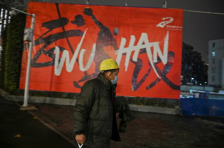 A man wearing a protective facemask walks along a street in Wuhan on January 26, 2020, a city at the epicentre of a viral outbreak that has killed at least 56 people and infected nearly 2,000