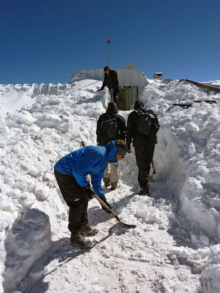 The ArTeMiS space camera team shovel snow to get into the APEX control building on the Chajnantor Plateau in northern Chile. In the foreground is Laurent Clerc, in the middle are Jérôme Martignac (left) and François Visticot (right), and in the