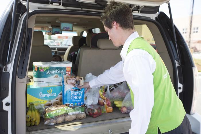 A Walmart associate loads groceries into the back of a car.