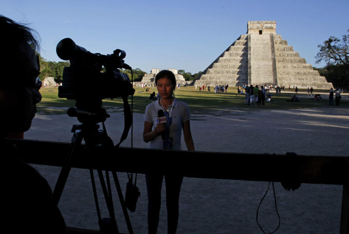 A journalist speaks in front of a TV camera in Chichen Itza, Mexico, Thursday, Dec. 20, 2012. Amid a worldwide frenzy of advertisers and new-agers preparing for a Maya apocalypse, one group is approaching Dec. 21 with calm and equanimity, the people whose ancestors supposedly made the prediction in the first place. (AP Photo/Israel Leal)