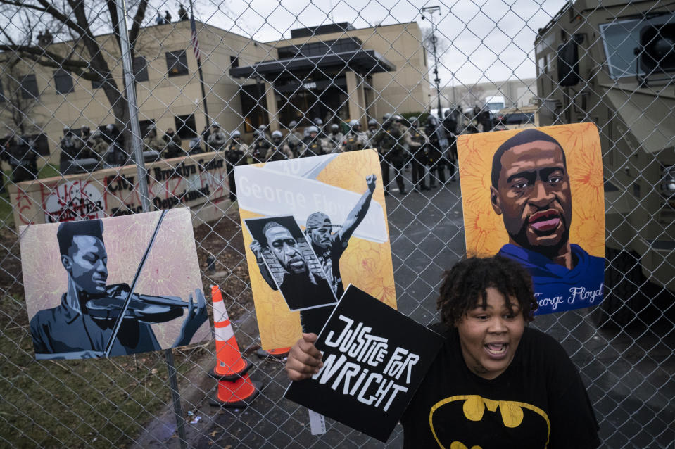 A demonstrator holds a sign along a perimeter fence guarded by law enforcement officers during a protest over Sunday's fatal shooting of Daunte Wright during a traffic stop, outside the Brooklyn Center Police Department, Wednesday, April 14, 2021, in Brooklyn Center, Minn. At right on the fence is an image of George Floyd. (AP Photo/John Minchillo)