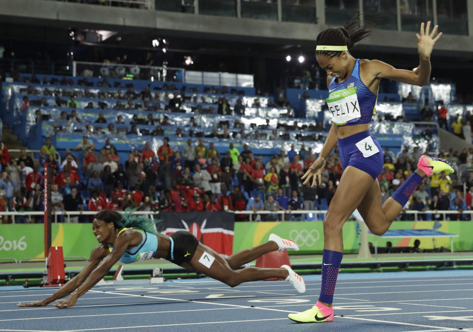 FILE - In this Aug. 15, 2016, file photo, Bahamas' Shaunae Miller-Uibo falls over the finish line to win gold ahead of United States' Allyson Felix, right, in the women's 400-meter final during the athletics competitions of the 2016 Summer Olympics at the Olympic stadium in Rio de Janeiro, Brazil. Miller-Uibo won gold in Rio with a dive at the finish of the 400 meters. She's diving in at the Tokyo Games with plans to not only defend her title but chase after gold in the 200 meters. (AP Photo/Matt Slocum, File)