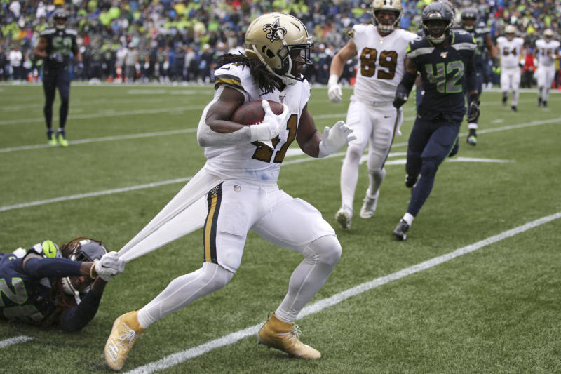 Seattle Seahawks' Shaquill Griffin, left, grabs hold of a piece of uniform as he tries to stop New Orleans Saints' Alvin Kamara on a run during the second half of an NFL football game Sunday, Sept. 22, 2019, in Seattle. (AP Photo/Scott Eklund)