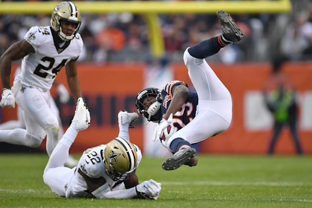 The Bears' Tarik Cohen (29) goes for a ride after getting tackled by Saints defensive back Chauncey Gardner-Johnson. (Getty Images)