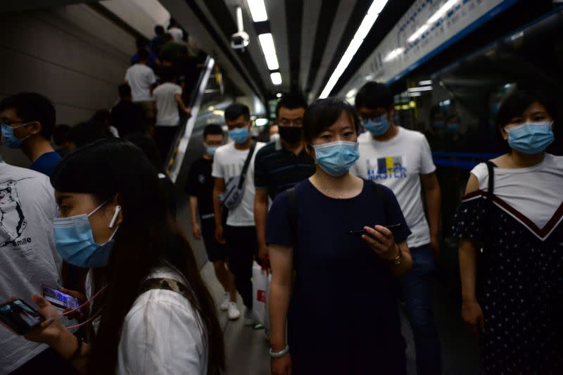 People wearing face masks walk inside a subway station during morning rush hour, following an outbreak of the novel coronavirus disease (COVID-19), in Beijing