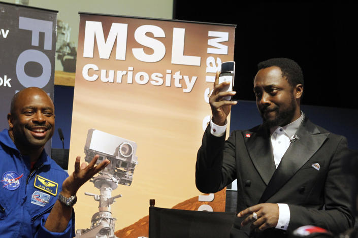 Musician will.i.am (R) uses his mobile phone to take a photograph as NASA astronaut Leland Melvin looks on during a news conference at NASA's Jet Propulsion Lab in Pasadena, California August 5, 2012. will.i.am attended the conference to promote science and technology education. The Mars Science Lab Curiosity rover is set to land on Mars in the late evening of August 5, 2012. REUTERS/Fred Prouser (UNITED STATES - Tags: SCIENCE TECHNOLOGY ENTERTAINMENT)