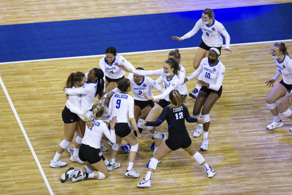Kentucky rushes the court celebrating a win over Washington in four sets during a semifinal in the NCAA women's volleyball championships Thursday, April 22, 2021, in Omaha, Neb. (AP Photo/John Peterson)