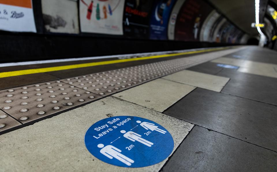 General view of sign on the floor on the London Underground for keeping 2 meters when boarding